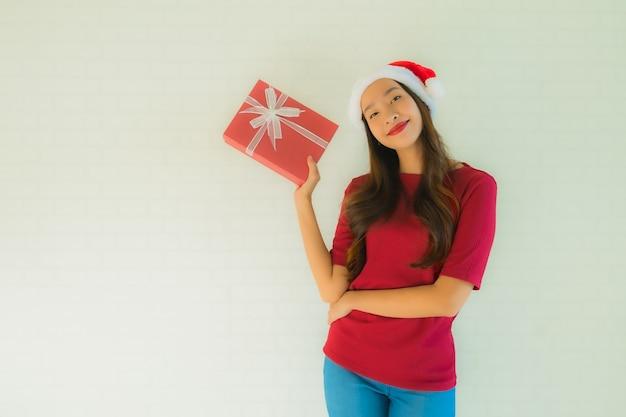 Retrato bela jovem asiática usar chapéu de papai noel com caixa de presente