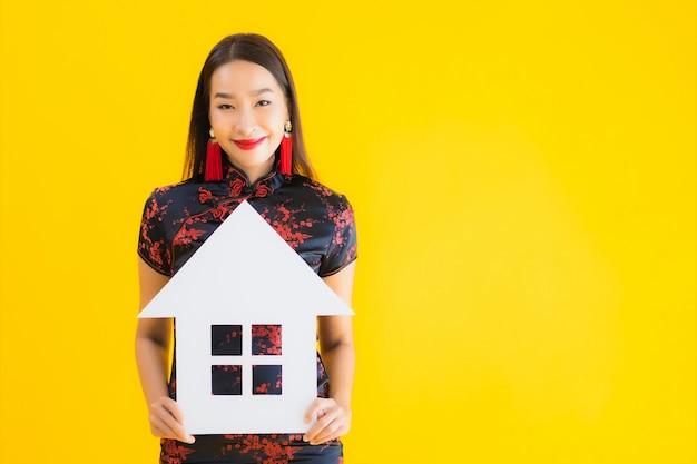 Retrato bela jovem asiática usar sinal de mostrar vestido chinês casa
