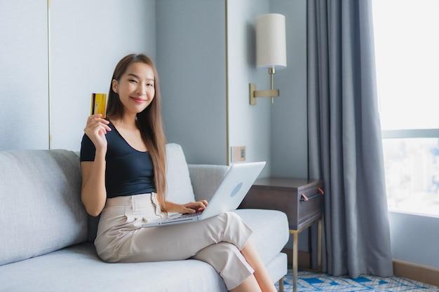 Retrato bela jovem asiática usar telefone móvel esperto ou laptop com cartão de crédito no sofá na sala de estar