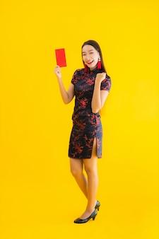 Retrato bela jovem asiática usar vestido chinês com ang pao ou letra vermelha com dinheiro