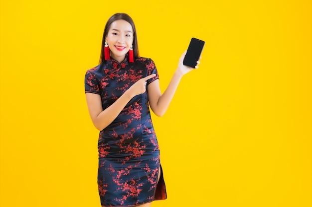 Retrato bela jovem asiática usar vestido chinês usar telefone móvel esperto