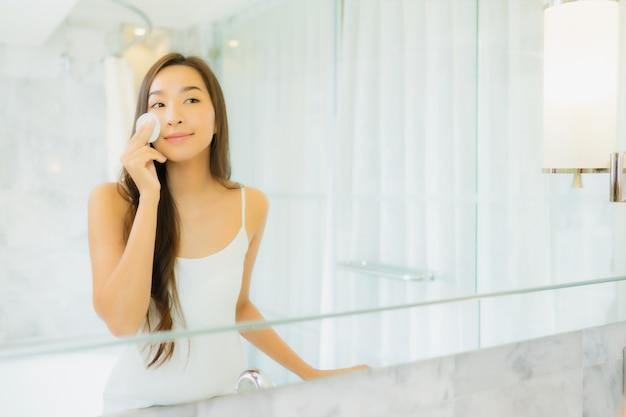 Retrato bela jovem asiática verifica e compõe o rosto