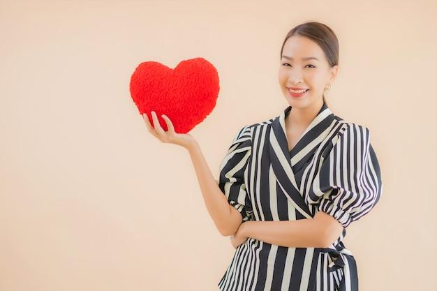 Retrato bela jovem mulher asiática com almofada de coração