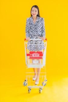 Retrato bela jovem mulher asiática com carrinho de compras para compras no amarelo