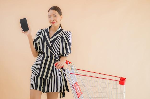 Retrato bela jovem mulher asiática com carrinho de compras