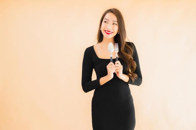 Retrato bela jovem mulher asiática com colher e garfo