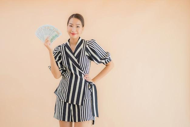 Retrato bela jovem mulher asiática com dinheiro e dinheiro