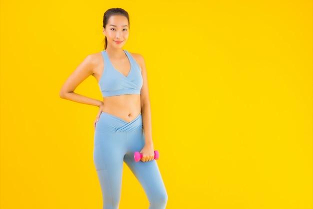 Retrato bela jovem mulher asiática com halteres e sportwear amarelo