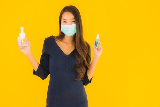 Retrato bela jovem mulher asiática com máscara e álcool