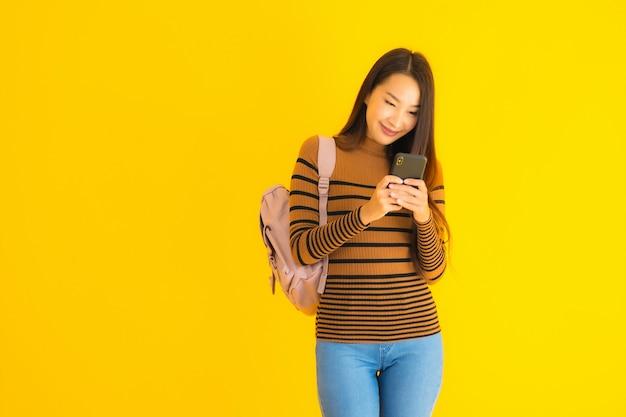 Retrato bela jovem mulher asiática com mochila usa smartphone