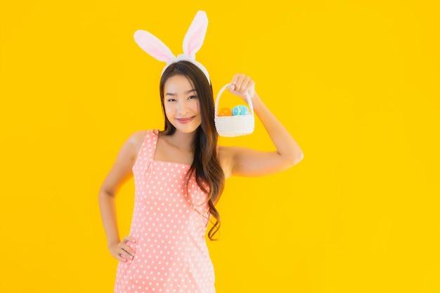 Retrato bela jovem mulher asiática com orelhas de coelho com ovos de páscoa