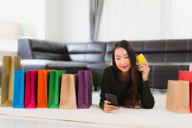 Retrato bela jovem mulher asiática com sacola de compras e cartão de crédito