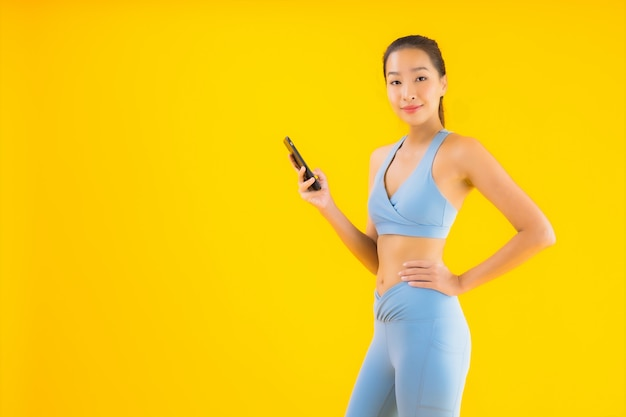 Retrato bela jovem mulher asiática com telefone móvel esperto amarelo isolado