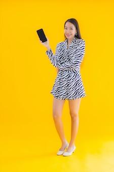 Retrato bela jovem mulher asiática com telefone móvel esperto e cartão de crédito em amarelo