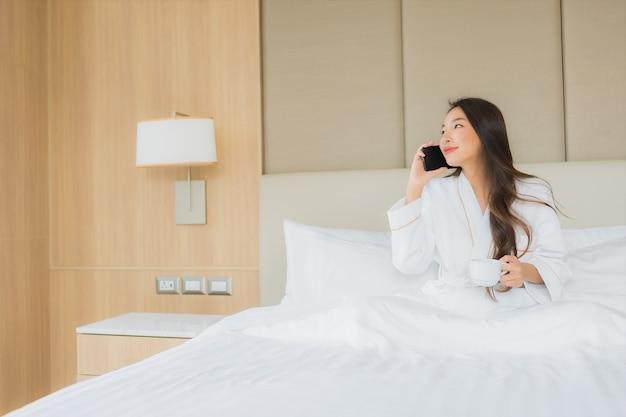 Retrato bela jovem mulher asiática com telefone móvel esperto no quarto