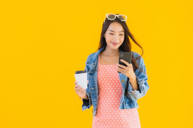 Retrato bela jovem mulher asiática com xícara de café e smartphone