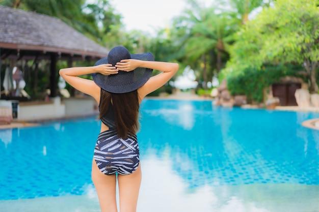 Retrato bela jovem mulher asiática em torno da piscina