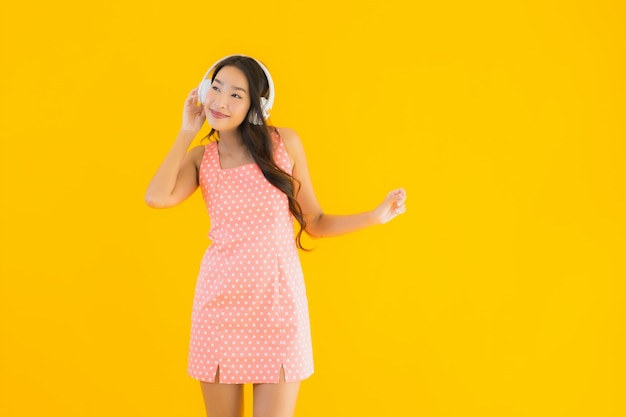 Retrato bela jovem mulher asiática ouve música com fone de ouvido