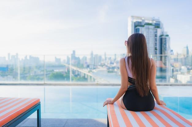 Retrato bela jovem mulher asiática relaxa lazer ao redor da piscina