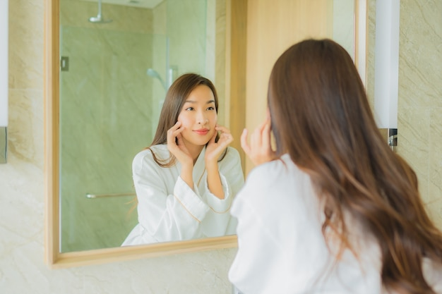 Retrato bela jovem mulher asiática verificar rosto no banheiro