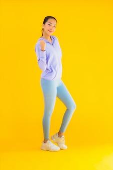 Retrato bela mulher asiática jovem esporte pronto para exercício amarelo