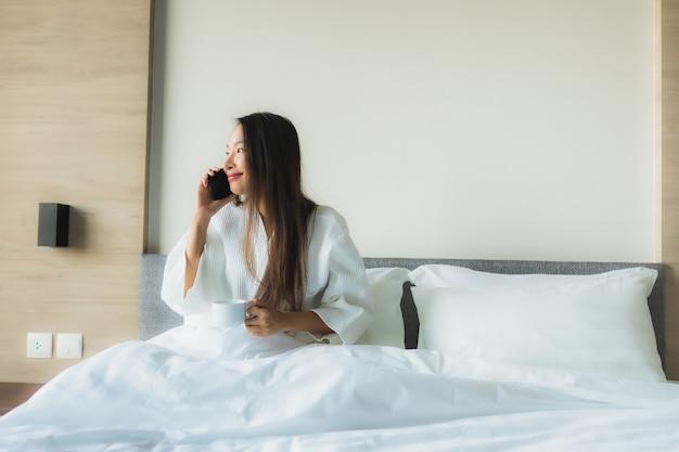 Retrato belas jovens asiáticas sorriso feliz com café e telefone móvel
