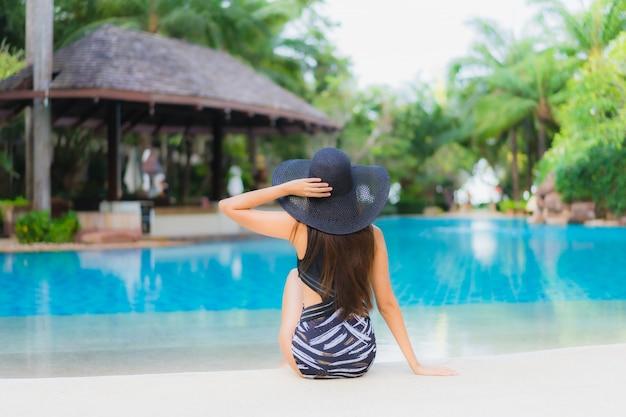 Retrato belas jovens asiáticas sorriso feliz relaxar ao redor da piscina