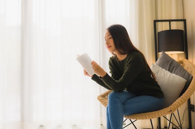 Retrato belas jovens mulheres asiáticas lendo livro e sentado na cadeira do sofá