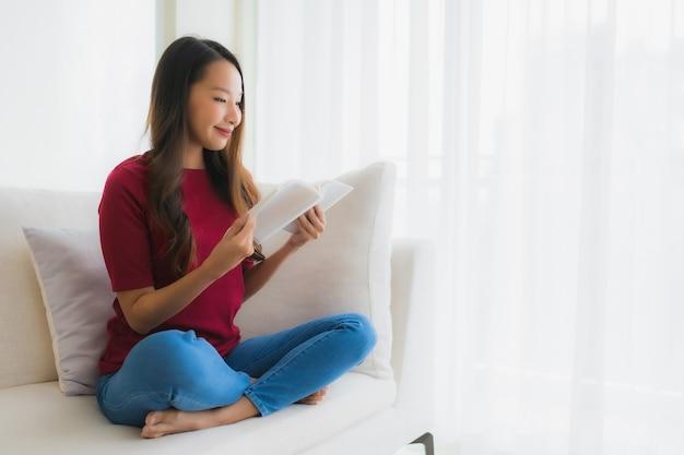 Retrato belas jovens mulheres asiáticas ler livro na cadeira do sofá