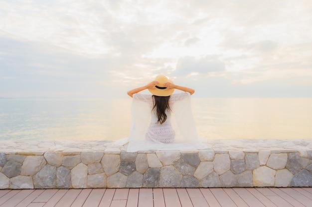 Retrato belas jovens mulheres asiáticas sorriso feliz relaxar ao redor do mar praia oceano