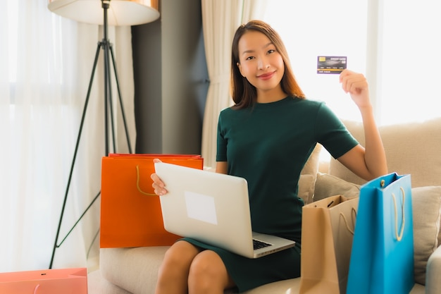 Retrato belas jovens mulheres asiáticas usando computador laptop com cartão de crédito para compras on-line