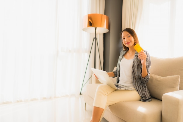 Retrato belas jovens mulheres asiáticas usando computador portátil ou telefone móvel e inteligente com cartão de crédito para compras on-line