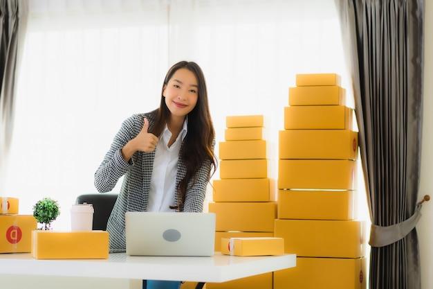 Retrato belo trabalho de mulher de negócios asiáticos em casa com o celular portátil com caixa de papelão pronta para o transporte