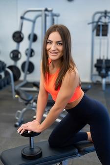 Retrato bonito apto mulher levantando halteres no banco no ginásio