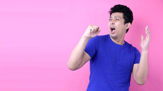 Retrato bonito ásia homem cantando alto em pé no fundo rosa no estúdio