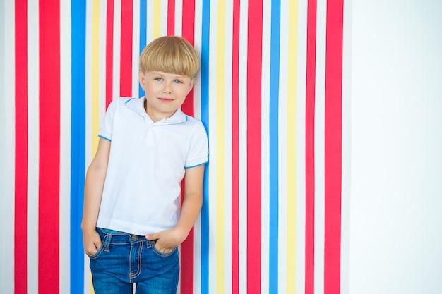 Retrato bonito da criança acima no colorido. adorável menino de pé perto da parede.