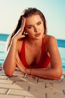 Retrato bonito da mulher em uma piscina nas férias