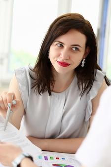 Retrato bonito da mulher no local de trabalho que examina