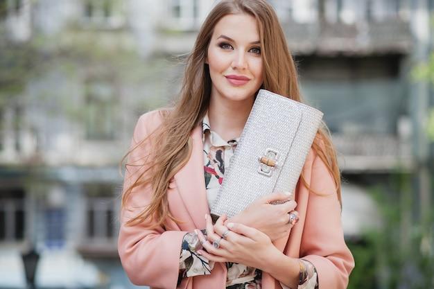 Retrato bonito de mulher atraente e sorridente, caminhando pelas ruas da cidade com casaco rosa, tendência da moda de primavera segurando a bolsa