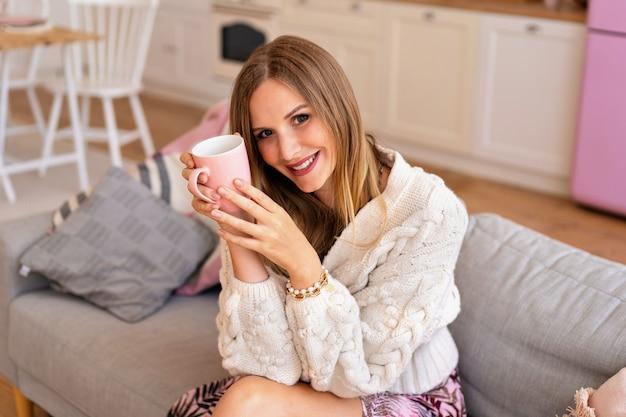Retrato bonito de uma bela loira alegre jovem loira, aproveitando o tempo em casa.