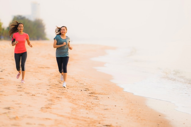 Retrato, bonito, desporto jovem, mulher asian, executando, e, exercício, praia, perto, mar oceano, em, amanhecer, ou, pôr do sol, tempo