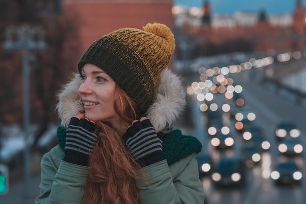 Retrato bonito do inverno da jovem mulher no cenário nevado do inverno. menina bonita ruiva andando em uma cidade de noite de inverno