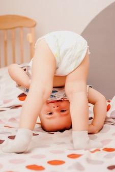 Retrato bonito do menino pequeno feliz da criança que joga de cabeça para baixo.