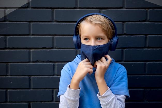 Retrato bonito fresco loiro caucasiano garotinho em casual capuz azul e máscara protetora médica fica a rua da cidade contra uma parede de tijolos cinza, ouvindo música em fones de ouvido, bom humor, mantenha a calma.