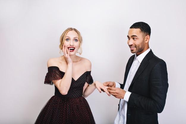 Retrato bonito homem alegre na camisa branca, fazendo a proposta de casamento com uma jovem atraente atônita em um vestido de noite de luxo. comemoração, namorados, amantes, juntos.