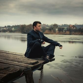 Retrato bonito homem sério no casaco ao ar livre no outono