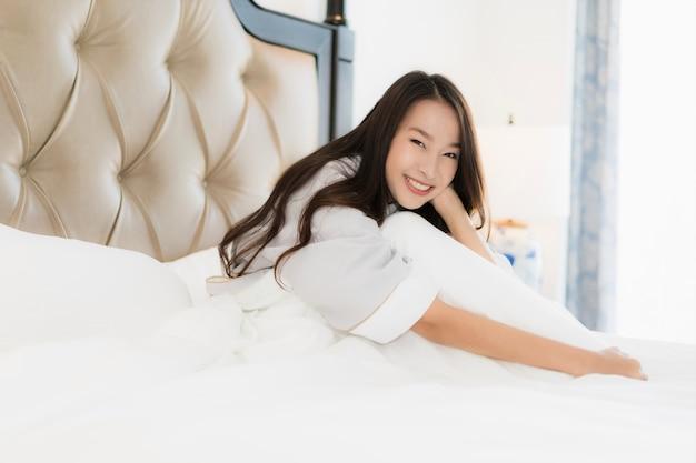 Retrato, bonito, jovem, mulher asian, acorde feliz, e, sorrizo, cama, em, quarto, interior
