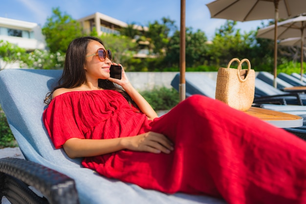 Retrato, bonito, jovem, mulher asian, com, telefone pilha, ou, telefone móvel, ao redor, piscina, em, hotel, recurso