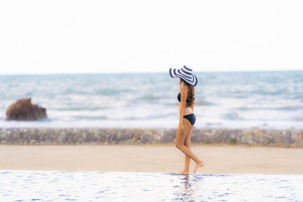 Retrato, bonito, jovem, mulher asian, desgaste, biquíni, ao redor, piscina, em, hotel, recurso, quase, mar oceano, praia