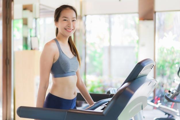 Retrato, bonito, jovem, mulher asian, exercício, com, equipamento aptidão, em, ginásio, interior